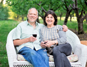 Ludger and Julie, holding glasses of red wine and sitting on a white wicker chair in an orchard row with green trees on both sides behind them.