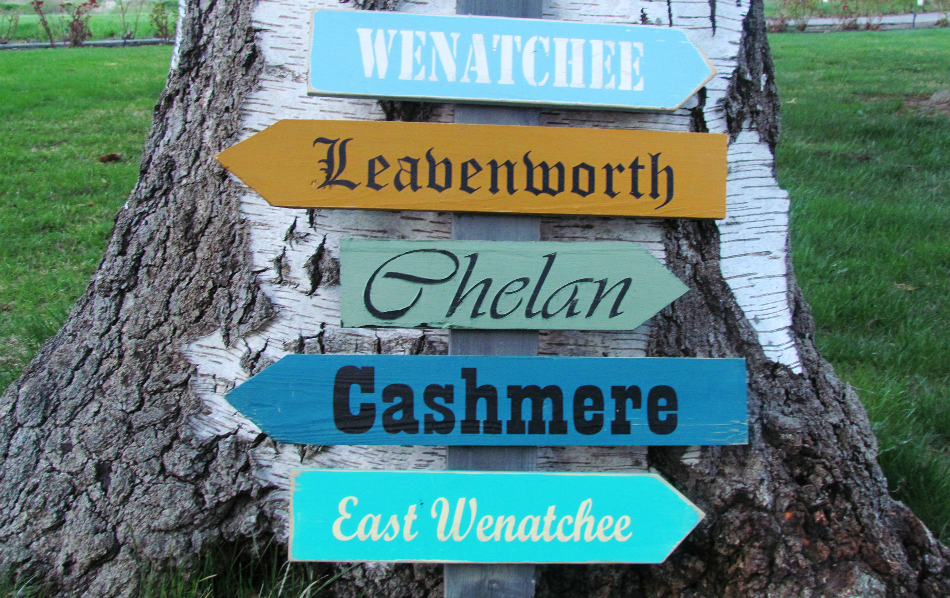 Wooden sign leaning against a tree pointing directions to Wenatchee, Leavenworth, Chelan, Cashmere and East Wenatchee