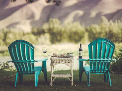 two chairs overlook the Wenatchee River from a grassy lawn with wine and charcuterie