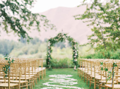 Flower petals line the grassy isle to down to a wedding altar and is surrounded by rustic wooden chairs.