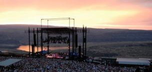 very large crowd in front of gorge ampitheater stage at sunset with river and gorge in background
