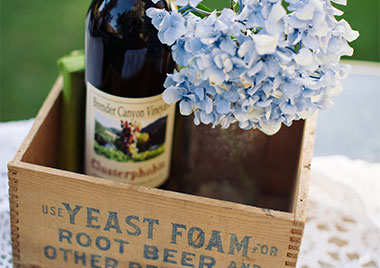 Bottle of Brender Canyon wine in an antique wooden box with blue hydrangea flowers