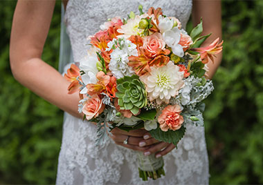 Bride's hands holding bouquet of white and orange flowers and green succulents