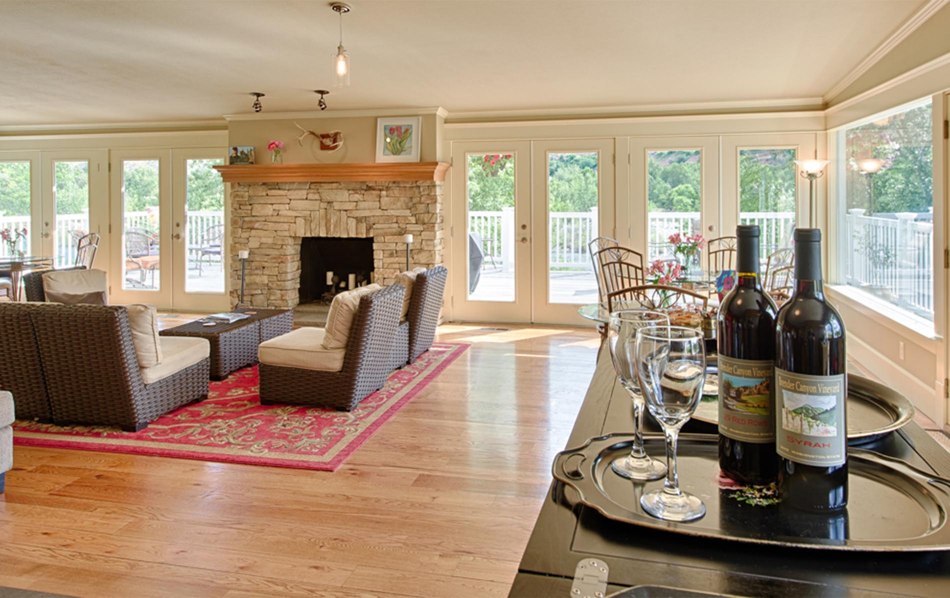 wine room displays our estate wines with the warm lounge and sandstone fireplace behind the wine bar – large French doors