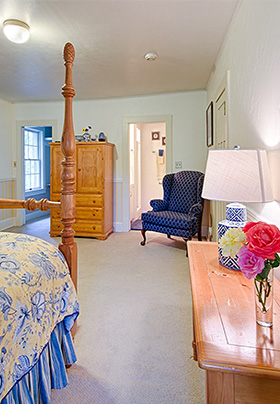 Room decorated in soft blues and yellows with a lovely four-poster Queen bed that accents the room with natural pine wood furniture
